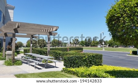 Aluminum dining table under light shading pergola, Camarillo, CA - stock photo