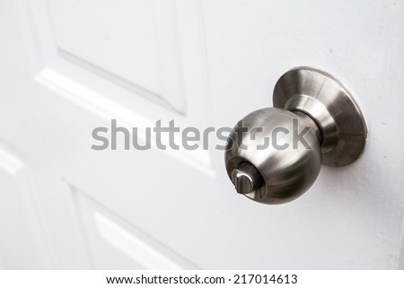 Aluminum door knob on the white door skin. - stock photo