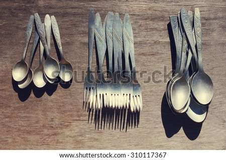 Aluminum spoons, forks. Old aluminum spoons and forks on a wooden surface. Old tableware - stock photo