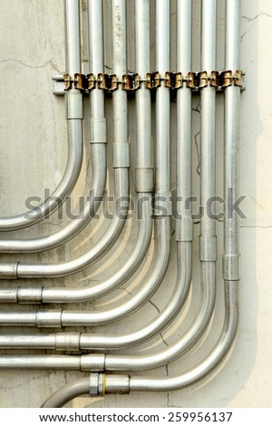 Aluminum tubing for wire protection lined up on old concrete wall . - stock photo