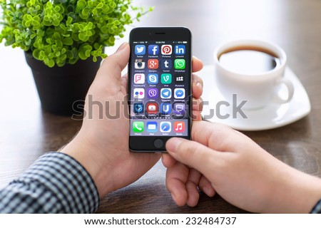 Alushta, Russia - November 20, 2014: A set of programs from famous brands of social networking on the phone iPhone 6 in man hands. iPhone 6 was created and developed by the Apple inc.  - stock photo