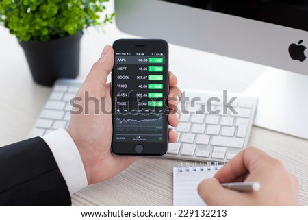 Alushta, Russia - November 3, 2014: Businessman holding a iPhone 6 Space Gray with application Stocks of Apple on the screen. iPhone 6 was created and developed by the Apple inc. - stock photo