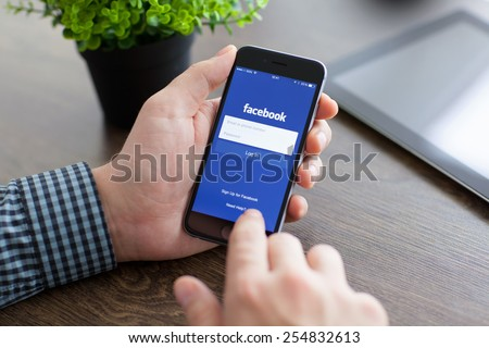 Alushta, Russia - November 21, 2014: Man holding a iPhone 6 Space Gray with social networking service Facebook on the screen. iPhone 6 was created and developed by the Apple inc. - stock photo