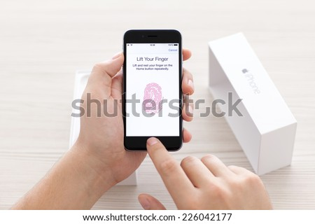 Alushta, Russia - October 23, 2014: Man scans the fingerprint sensor Touch ID on iPhone 6 Space Gray over the table. Touch ID was created and developed by the Apple inc. - stock photo