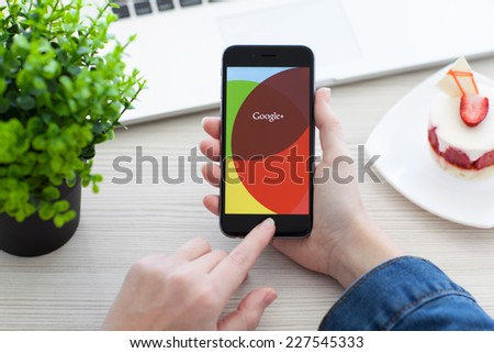 Alushta, Russia - October 28, 2014: Woman holding a iPhone 6 Space Gray with social networking service Google+ on the screen. iPhone 6 was created and developed by the Apple inc. - stock photo
