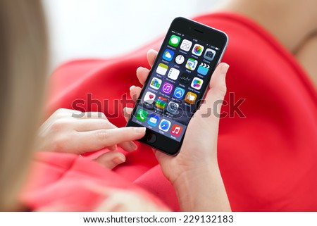 Alushta, Russia - October 29, 2014: Woman holding new iPhone 6 Space Gray in the hand. iPhone 6 was created and developed by the Apple inc. - stock photo