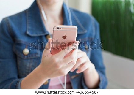 Alushta, Russia - October 27, 2015: Woman with headphones holding in the hand iPhone6S Rose Gold. iPhone 6S Rose Gold was created and developed by the Apple inc. - stock photo