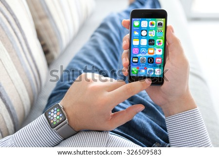 Alushta, Russia - September 24, 2015: Man hand with Apple Watch holding iPhone. Apple Watch was created and developed by the Apple inc. - stock photo