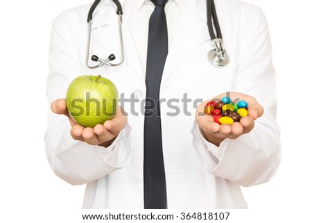 Always a choice there. Cropped shot of a doctor holding a green apple and pills in his hands  - stock photo