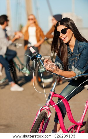 Always in touch. Beautiful young smiling woman leaning at her bicycle and looking at her mobile phone while her friends talking in the background  - stock photo