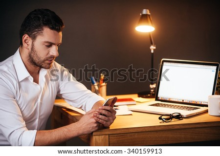 Always in touch. Confident young man texting on his smart phone while sitting at his working place at night time - stock photo
