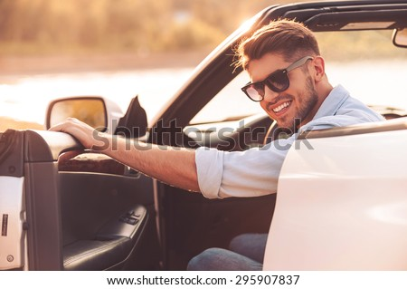 Always ready for good driving. Cheerful young man smiling at camera and closing the door while sitting inside of his white convertible - stock photo