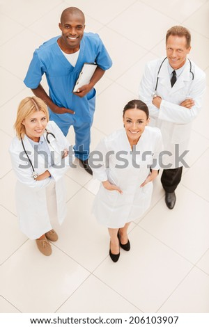 Always ready to help. Top view of four confident doctors standing close to each other and smiling - stock photo