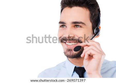 Always ready to help you. Portrait of handsome young male operator adjusting his headset and smiling while standing against white background - stock photo
