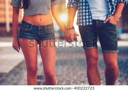 Always together. Close-up of beautiful young loving couple holding hands while walking along the street  - stock photo