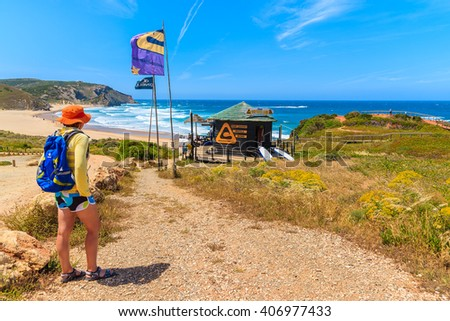 AMADO BEACH, PORTUGAL - MAY 15, 2015: Young woman tourist on walking path to Praia do Amado beach in spring, Algarve region, Portugal. This area is famous surfing place in whole Portugal. - stock photo