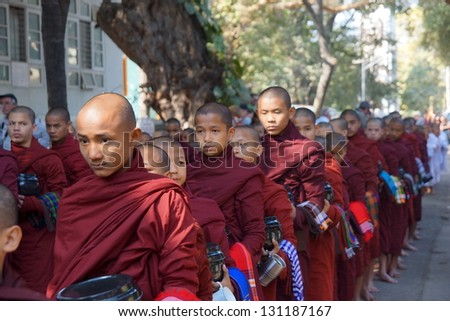 AMARAPURA, MYANMAR - JAN 15 : Buddhist novices walk to collect alms and offerings on January 15, 2013 in Amarapura near Mandalay, Myanmar. This procession is held every day. - stock photo