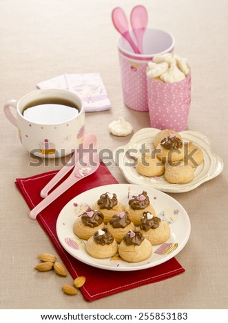 amaretti biscuits with chocolate cream on a plate decorated with hearts sandy background - stock photo