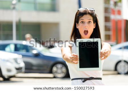 Amazed and exited sales business woman in luxury car trade fair. female seller showing tablet touch pad empty screen.  Commercial offer, vehicle rental and promotion concept. - stock photo