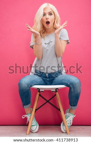 Amazed charming woman sitting on the chair over pink background - stock photo