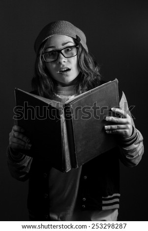 Amazed girl with a book. black and white - stock photo