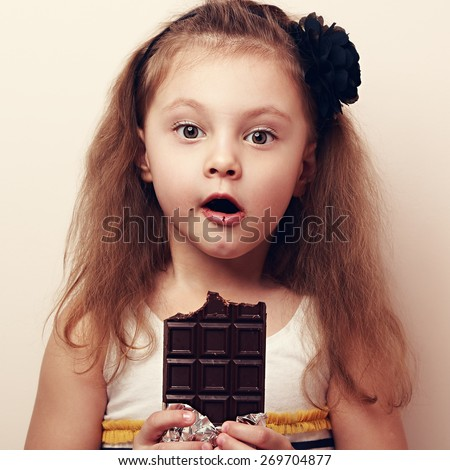 Amazed kid girl looking with open mouth holding dark chocolate. Vintage closeup portrait - stock photo