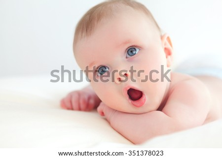 amazed little baby on a blanket  with mouth wide open - stock photo