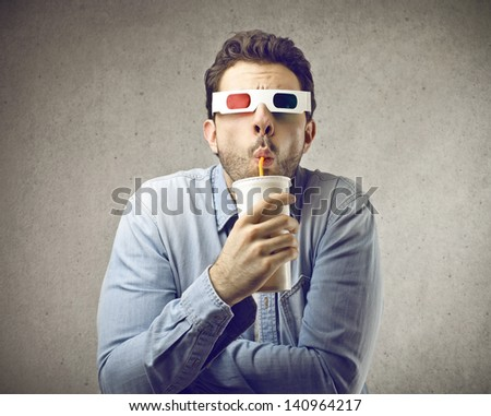 amazed man with 3D glasses watches movies while drinking - stock photo