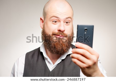 Amazed news! young bearded caucasian man reading message on his smart phone while standing isolated on studio background - stock photo