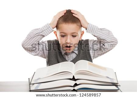 Amazed or surprised child boy reading education books at desk - stock photo