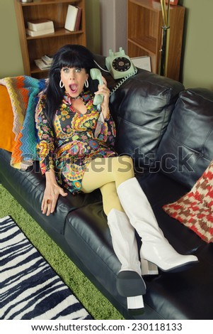 Amazed pretty woman on sofa holding telephone - stock photo