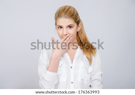 Amazed, scared, shocked. Young girl with hands on her mouth looking amazed. Beautiful young blonde girl in white shirt reacting surprised. - stock photo