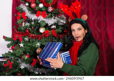 Amazed woman opening Christmas gift  home - stock photo