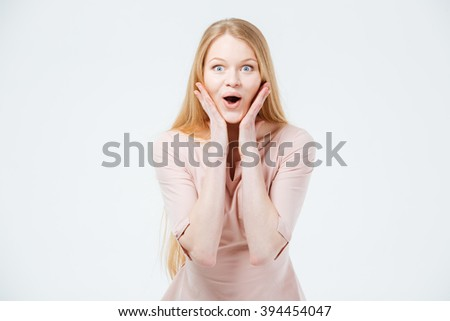 Amazed woman standing isolated on a white background - stock photo