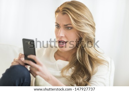 Amazed young Caucasian woman looking at mobile phone while relaxing on sofa - stock photo