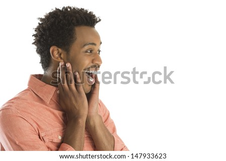 Amazed young man with hands on face looking at copy space against white background - stock photo