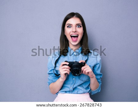 Amazed young pretty woman holding camera over gray background. Looking at camera - stock photo