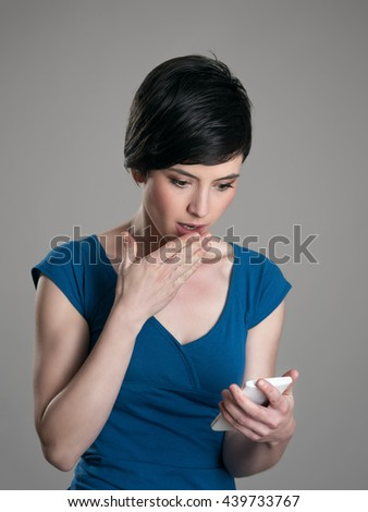 Amazed young short hair woman reading news on smart phone. - stock photo