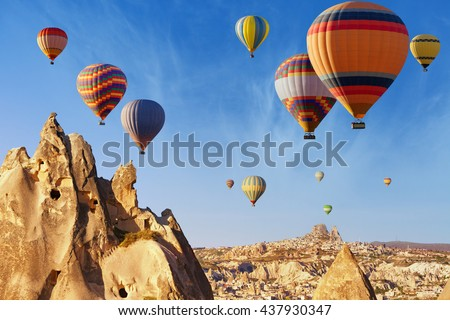 Amazing attraction and adventure in Kapadokya, hot air balloons flying above unusual rocky landscape in Cappadocia, Turkey - stock photo