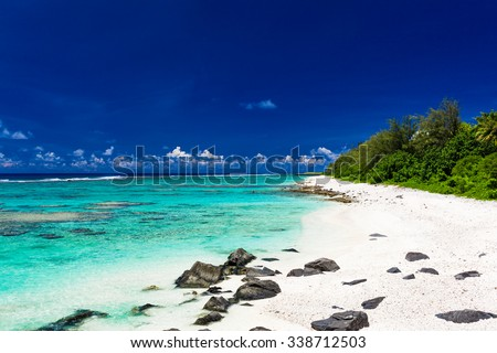 Amazing beach with white sand and black rocks on Rarotonga, Cook Islands - stock photo