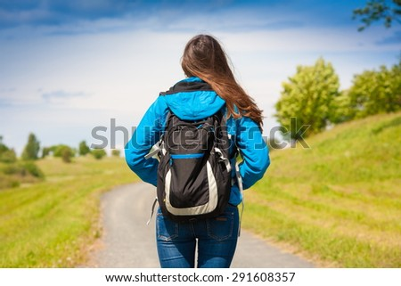 amazing beautiful elegance back haired hair woman blue jeans and jacket black backpack green landscape sport body way horizon portrait nature urban city - stock photo