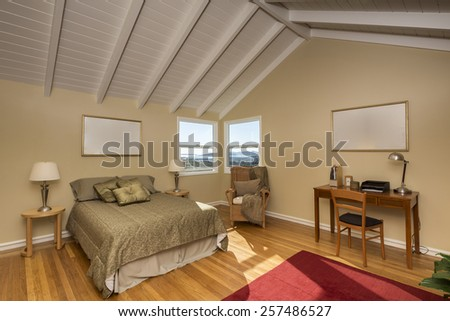 Amazing bedroom under peaked roof with wooden floor in beige, with bay view window, learning desk and pillows.  - stock photo
