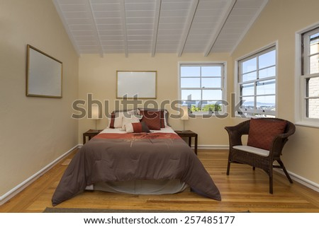 Amazing bedroom under peaked roof with wooden floor in beige, with bay view window, pillows and armchair.  - stock photo