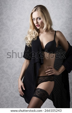 amazing blonde lady with sensual body and stylish make-up posing in glamour portrait with dark lingerie and sexy lace stockings  - stock photo