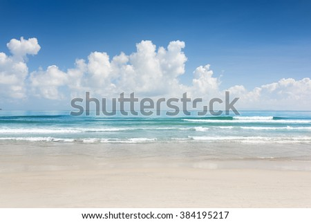 Amazing blue ocean and tropical white sand beach on sunny summer day. Beautiful sea view with azure crystal water. Scenic cloudy sky in background. - stock photo