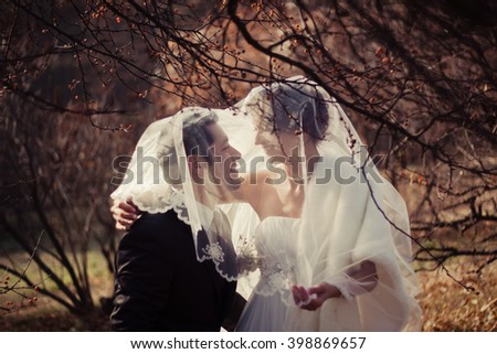 Amazing Bride and Groom embracing and looking at each other in the park. Multi ethnic couple : man of peruvian ethnicity (latin american and hispanic ethnicity) and woman of caucasian ethnicity. - stock photo