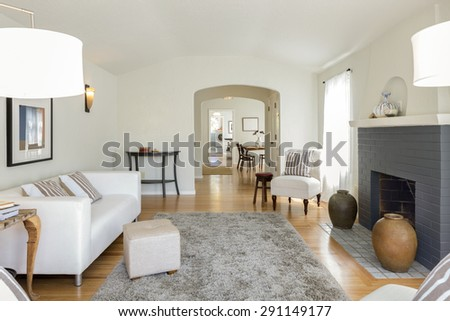 Amazing bright and harmonic Living Room Interior with white couch, chair, fire place, beautiful inlaid hardwood floor, arched niches and grey handwoven rug next to dining room. - stock photo