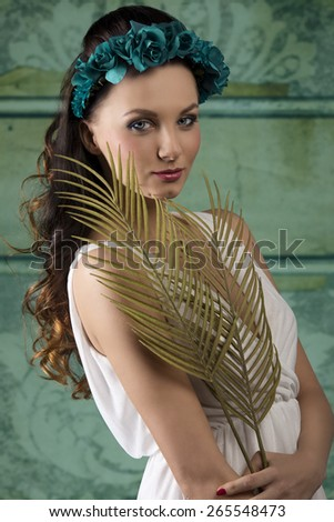 amazing brunette woman with spring style and long wavy hair posing with white dress, some flowers on head and palm leafs in the hands. Romantic expression  - stock photo