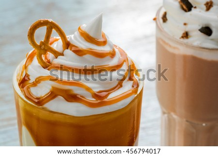Amazing caramel milkshake with cracknel on its top with the whipped topping. Massive glass for bigger portion of delicious drink. - stock photo