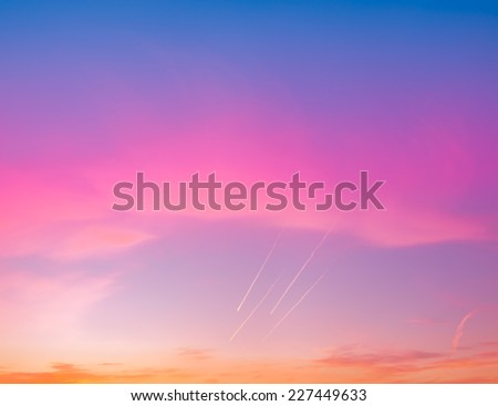 Amazing cloudscape with four airplane traces at cold sunset time. - stock photo